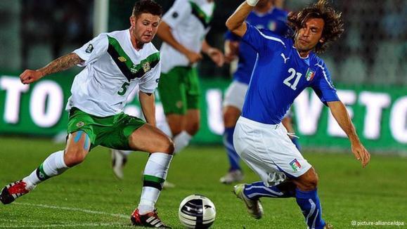الیویر نوردوود (چپ) از ایرلند در مصاف با آندره پیرلو، ستارهی تیم ملی فوتبال ایتالیا