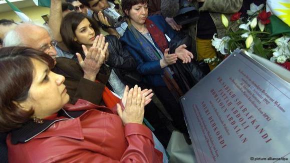 """مراسم پردهبردای از لوح یادبود قربانیان میکونوس در برلین در سال ۲۰۰۴. بر روی این لوح آمده: """"به قتل رسیده به دست حاکمان وقت ایران""""."""