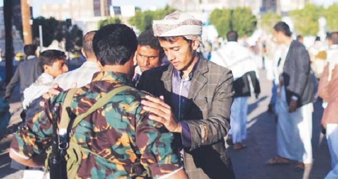 شورشی حوثی در حال تفتیش یک سرباز یمنی